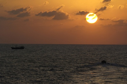 With the setting sun, HMCS OttawaÕs Naval Boarding Party approach a dhow in a Rigid Hull Inflatable Boat (RHIB) while conducting a boarding operation in the Arabian Gulf.