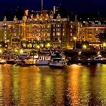 Empress hotel reflected in the Inner Harbour a night.